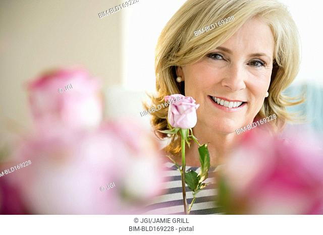Caucasian woman holding pink rose