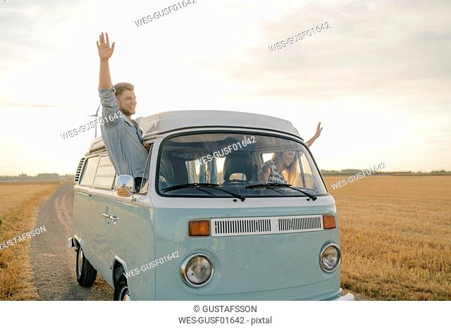 Happy couple leaning out of window of a camper van in rural landscape