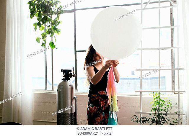 Young woman attaching bunting to balloon in design studio