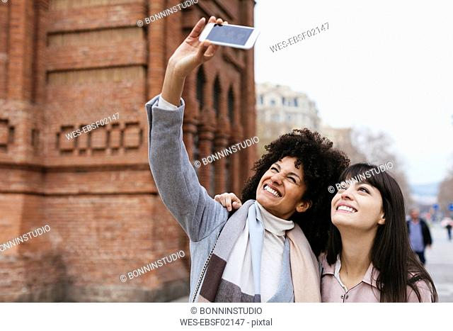 Spain, Barcelona, two happy women taking a selfie at a gate