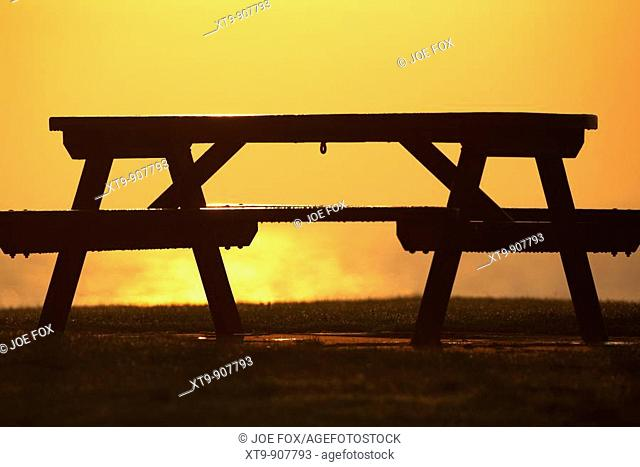 frozen wooden picnic table being thawed by morning sunshine county down Northern Ireland UK
