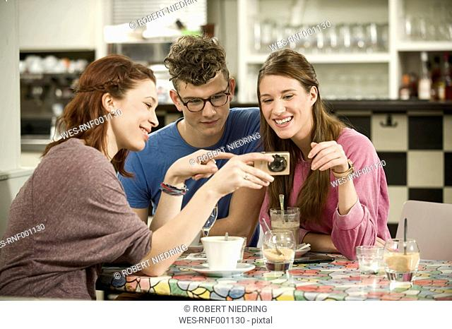 Germany, Bavaria, Munich, Young friends watching pictures in camera, smiling