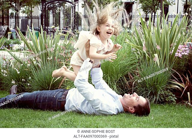 Father lying on grass, playfully lifting young daughter in air