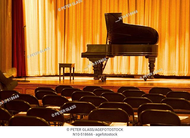 Grand piano on the stage of an empty auditorium
