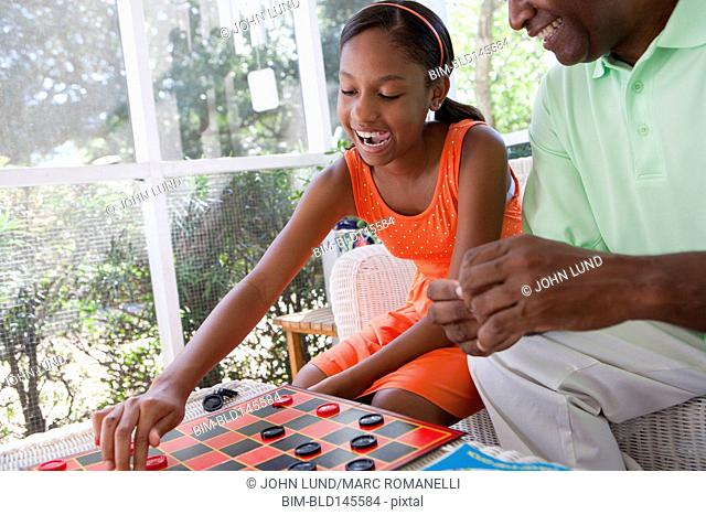 Black grandfather playing checkers with granddaughter