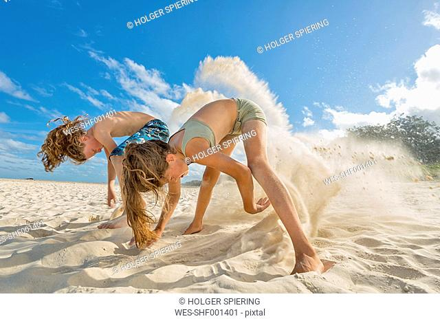 Australia, New South Wales, Pottsville, boy and girl digging in sand on beach