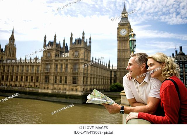 A middle-aged couple standing near the Houses of Parliament, looking along the river Thames