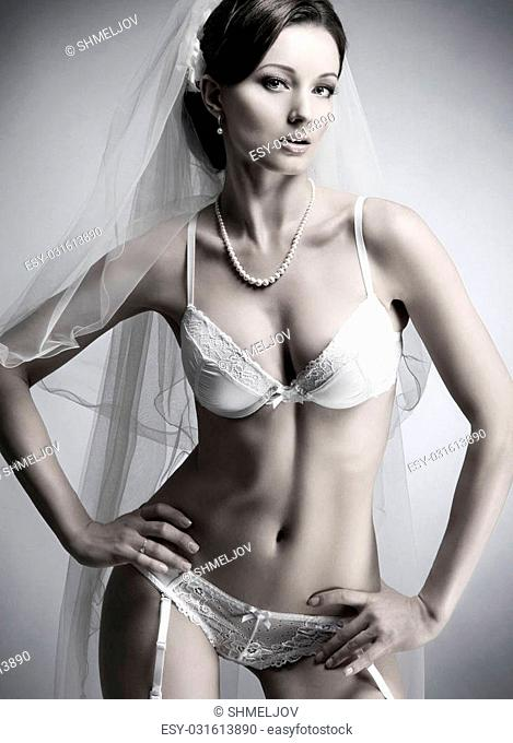 Black and white photo of young beautiful bride in sexy bridal lingerie