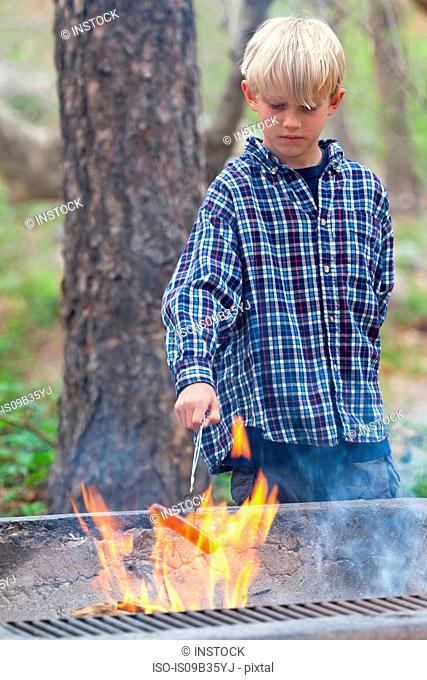 Boy barbecuing sausage on flaming grill in forest, Sedona, Arizona, USA