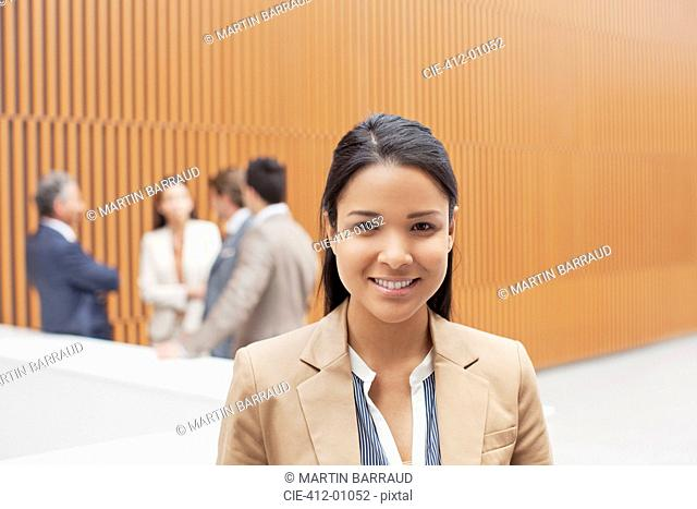 Portrait of smiling businesswoman with co-workers meeting in background