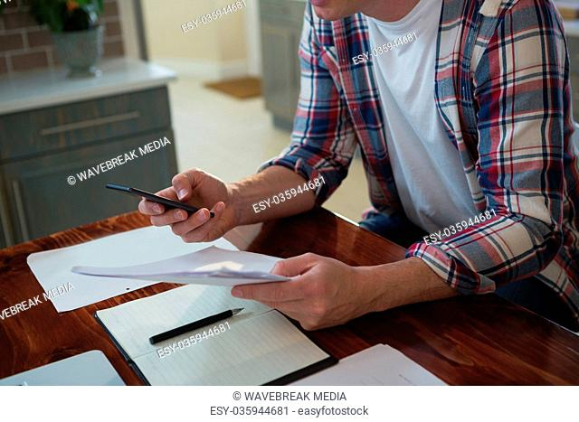Man using mobile phone and looking at document