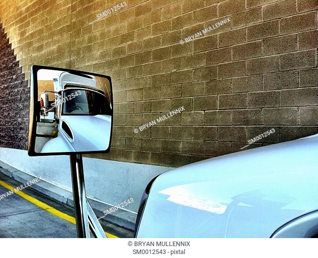 Reflection of commercial truck in its side view mirror (mobile image)