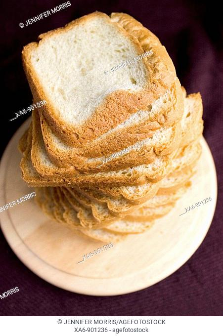 A stack of sliced white bread on a board