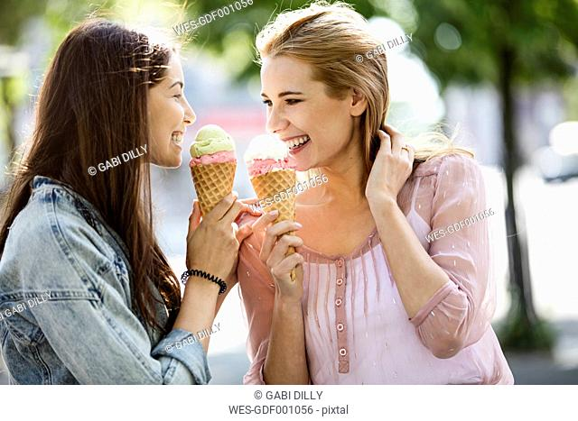 Two smiling young women with ice cream cones