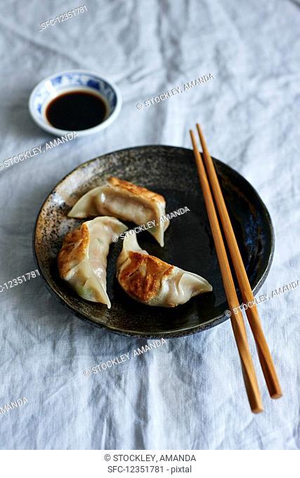 Gyoza with soy sauce and chopsticks (Japan)