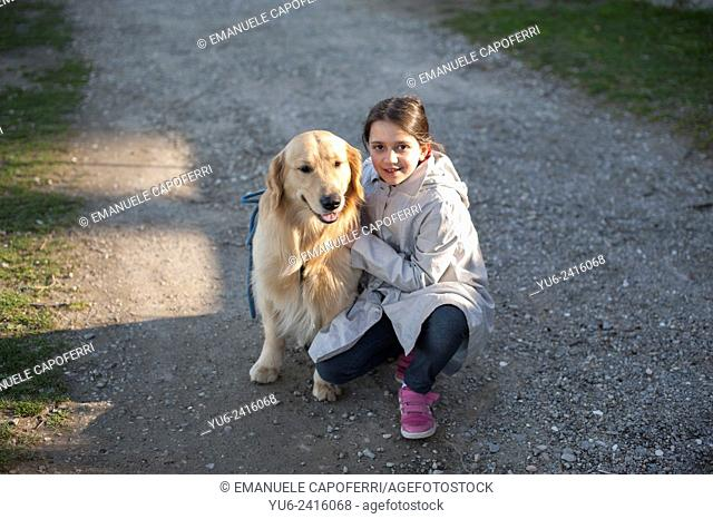 Little girl with her dog while walking by the lake, Ispra, Lake Maggiore, Lombardy, Italy