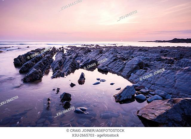 The rocky shore at Speke's Mill Mouth on the North Devon coast at sunset near Hartland, England