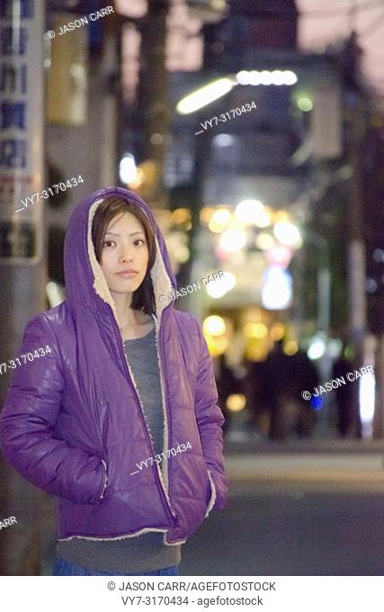 Japanese Girl poses on the street in Aoyama, Japan. Aoyama is a famous area about universities in Tokyo