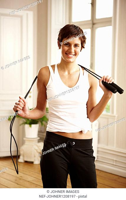 Woman holding skipping rope, portrait
