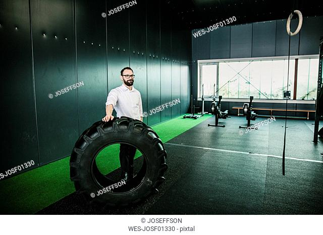 Businessman standing in gym holding truck tire