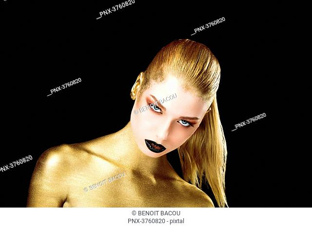 Portrait of a young woman, the body painted in gold, head down, eyes open