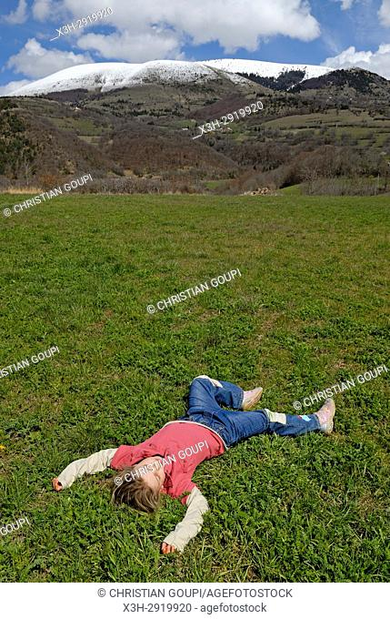 little girl lying on the back in meadow, Alps, France, Europe