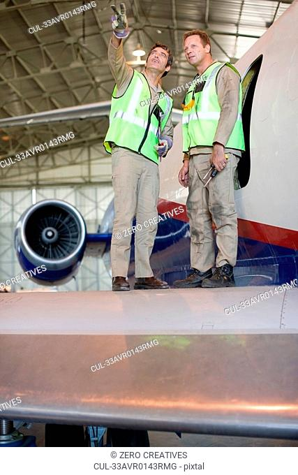 Aircraft workers talking on airplane