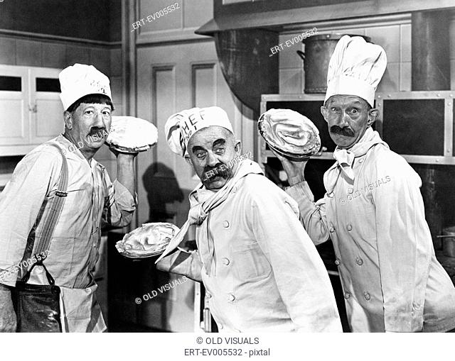 Three chefs holding pies for a fight in the kitchen All persons depicted are not longer living and no estate exists Supplier warranties that there will be no...