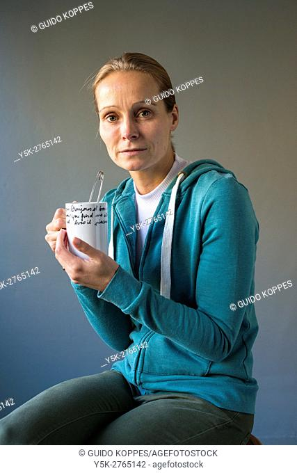 Tilburg, Netherlands. Studio portrait of a mid adult caucasian female drinking a cup of tea