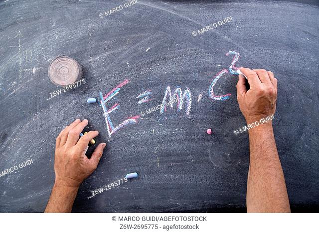 Representation of the energy formula designed with chalk on blackboard