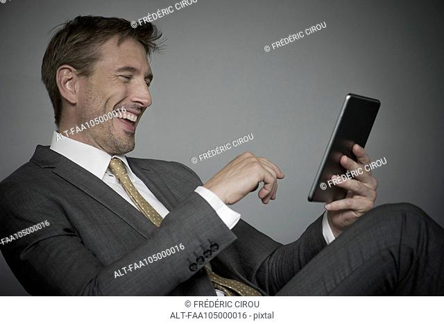Man laughing while using digital tablet