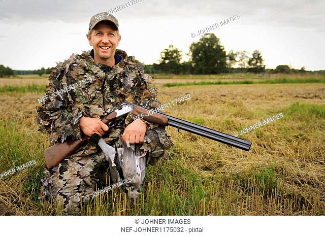 Hunter holding pigeon and rifle, smiling, portrait