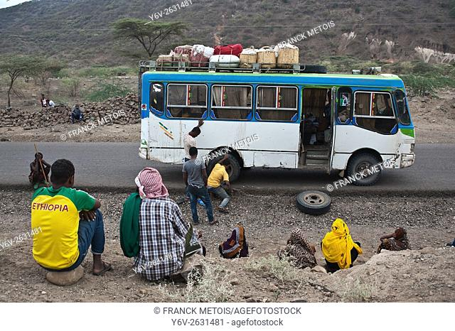 A bus employee is changing the flat tyre of the bus he is working in. The passengers are watching the young man changing the tyre