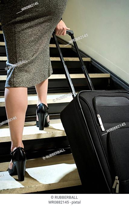 Low section view of a young woman walking with her luggage