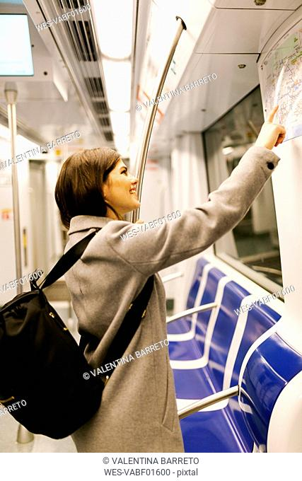 Spain, Barcelona, smiling young woman with backpack looking at map in underground train