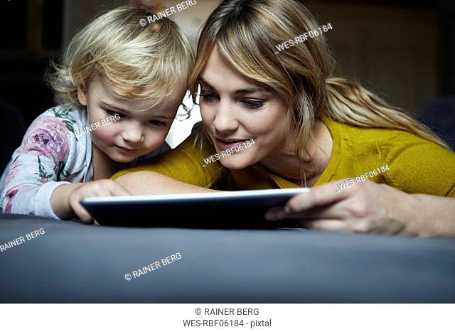 Portrait of mother and little daughter using tablet at home