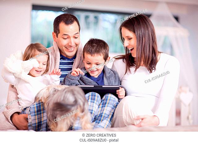 Parents, two children and dog looking at digital tablet