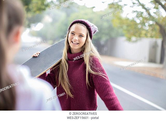 Smiling teenage girl holding skateboard meeting with friend