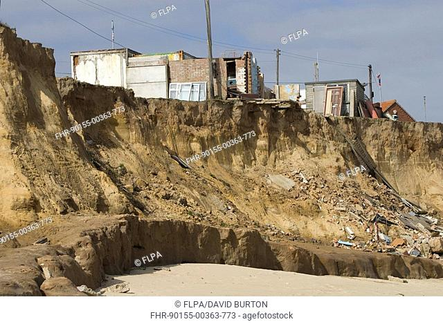Coastal erosion, cliffs eroded by sea, damaged buildings on clifftop, Happisburgh, North Norfolk, England