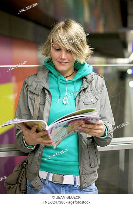 Young woman reading in magazine, waist up, front view