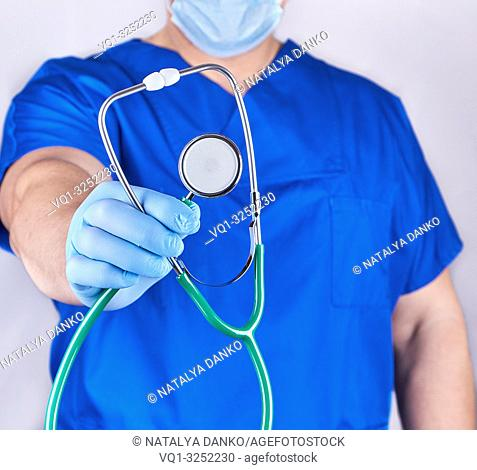 doctor in blue uniform and latex gloves holding a stethoscope, selective focus