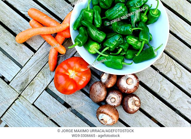 Small green peppers in white bowl carrots tomato and mushrooms o a wooden table