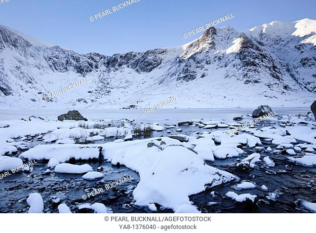 Cwm Idwal, Ogwen, Gwynedd, North Wales, UK, Europe  Snow scene with view across frozen Llyn Idwal lake to the Devil's Kitchen in mountains of Snowdonia National...