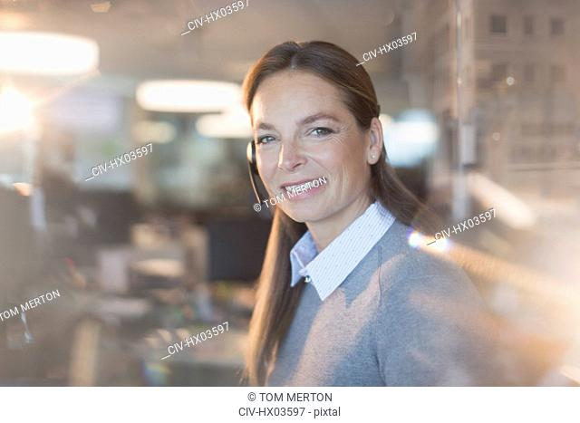 Portrait smiling, confident businesswoman wearing headset in office