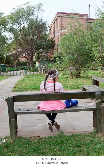 Young girl sitting on bench, rear view