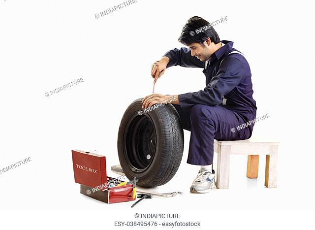 Portrait of mechanic repairing tyre