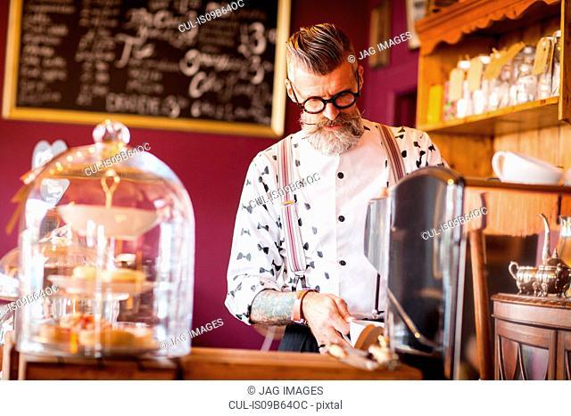 Quirky vintage senior man using coffee machine in tea room