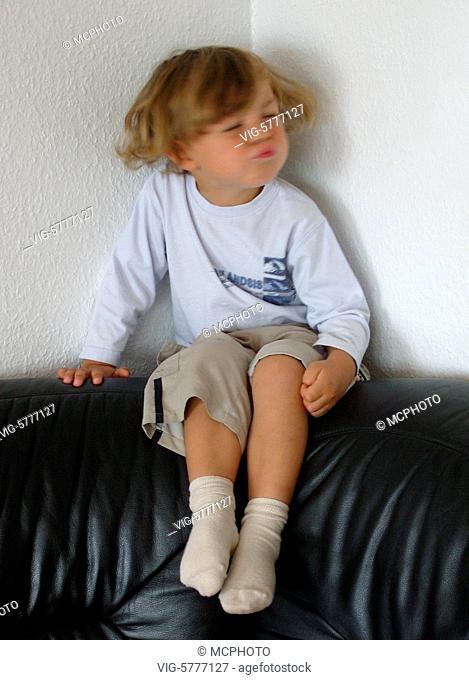Ein kleiner Junge sitzt auf dem Sofa und macht Faxen, 2006 - Germany, 12/09/2006