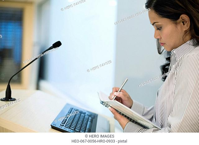 Businesswoman making notes at podium in seminar room