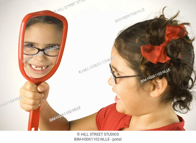 Young girl admiring herself in the mirror